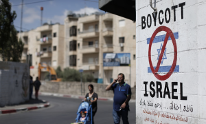Palestinians walk past a sign painted on a wall in the West Bank town of Bethlehem calling for a boycott of Israeli products from Jewish settlements. The international BDS (boycott, divestment and sanctions) campaign aims to exert pressure over Israel's occupation of the Palestinian territories. Photograph: Thomas Coex/AFP/Getty Images