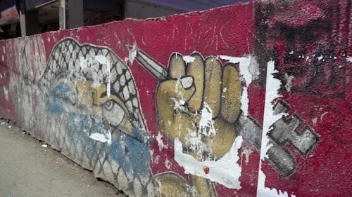 Graffiti in Ramallah showing masked Palestinian holding a key and pencil